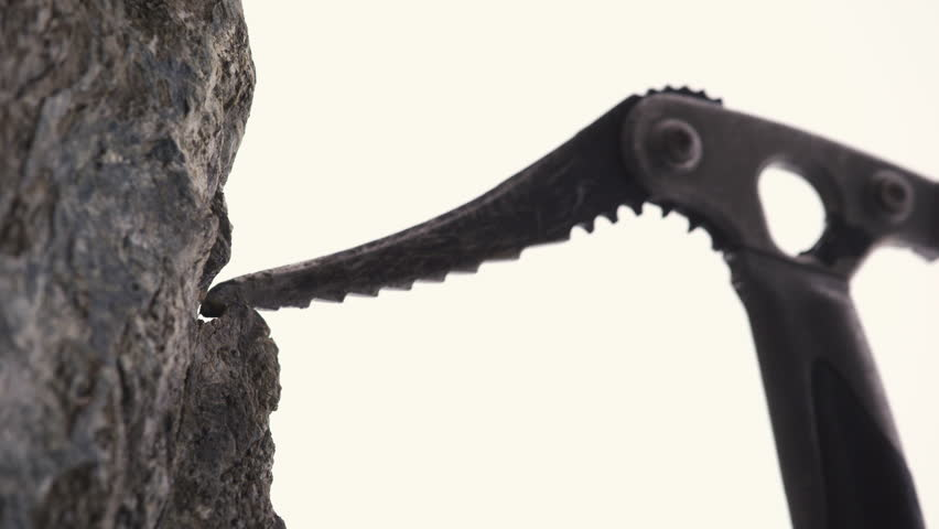 Close up of mountaineers axe hooking on a tiny rock edge.