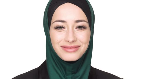 Portrait of positive arabic woman in traditional hijab posing looking on camera and laughing, over white background. Concept of emotions