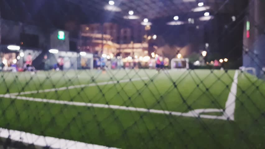 Blurred of people are playing futsal in artificial turf at night time after work.