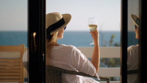 Cinemagraph - Young woman in hat and sunglasses having a rest with a glass of wine. She relaxing in arm-chair at the balcony overlooking the sea. Wind waving her hair
