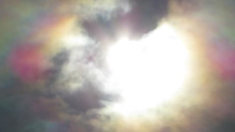 Clouds in sky shot into the sun during a solar eclipse causing sun flare light effects. Overlay footage.