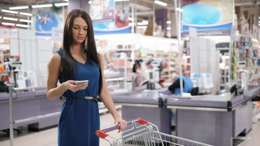 Woman using mobile phone while shopping in supermarket, trolley mall grocery shop store | Shutterstock HD Video #1007220151