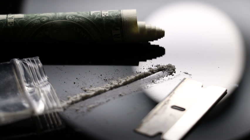 Macro drug and narcotic objects. Razor Blade, money and Coke. Party drugs on a table Cocaine abuse.