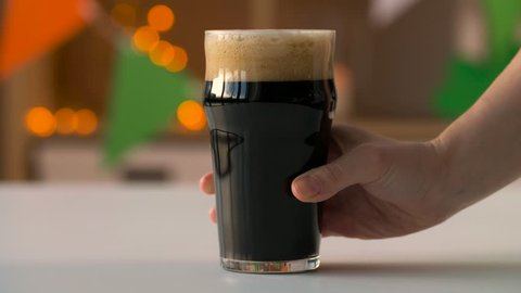 holidays, celebration and st patrick's day concept - female hand putting glass of dark draught beer on table