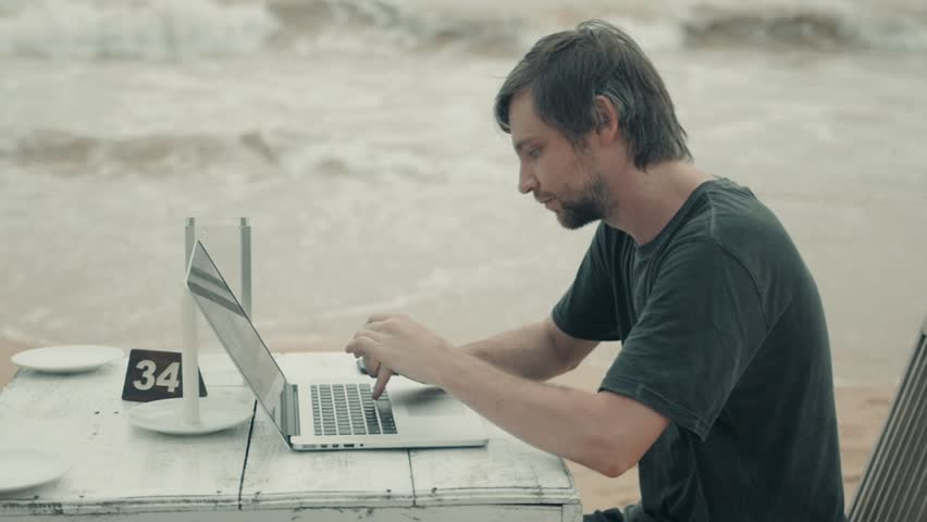 Man work on computer at the beach at sunset, freelancer programmer designer ICO application businessman man business