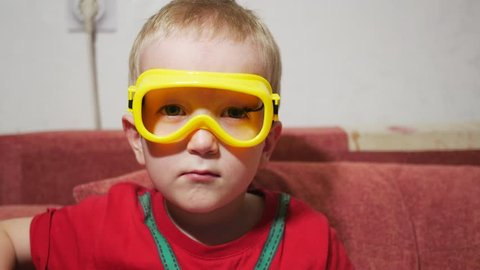 A child in safety glasses sits on the sofa at home and watches TV. Eat corn sticks and smile