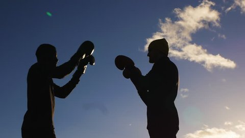 Boxing workout with trainer outdoors. Boxers in boxing gloves silhouettes sparring on blue cloudy sky background. Coach shows how to dodge a punch