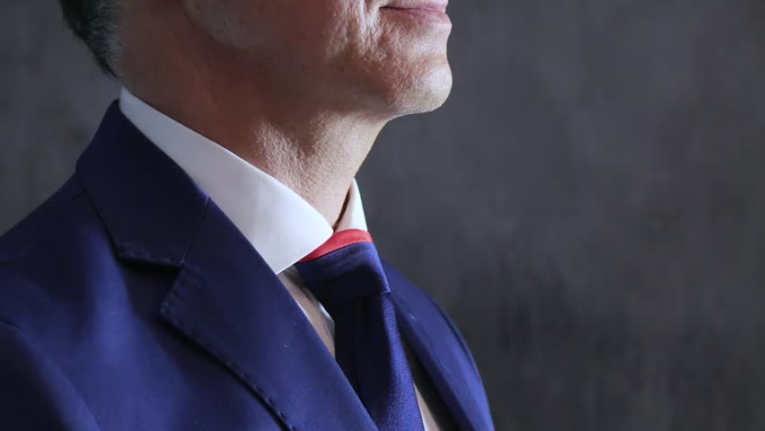 men in suit adjusts blue cravat on throat close-up on background of concrete wall, side view