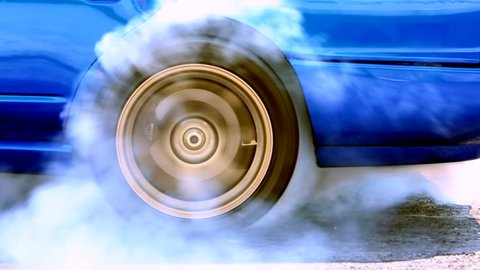 Car wheel spinning and creating of smoke, Drag racing car burns rubber,