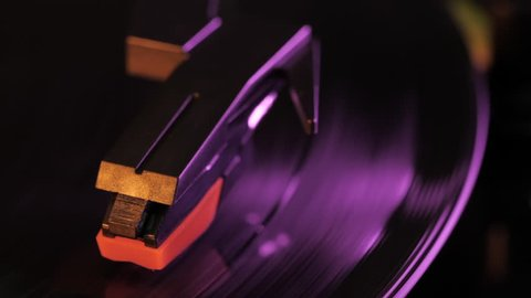 Record player turntable HD stock footage. A record player turntable with it's stylus running along a vinyl record. Neon violet light
