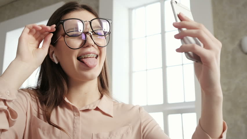Beautiful woman taking selfie using phone smiling. Attractive student with glasses searching best pose for selfie portrait. Trendy girl taking selfie photo on smart phone. Young girl in braces smiling