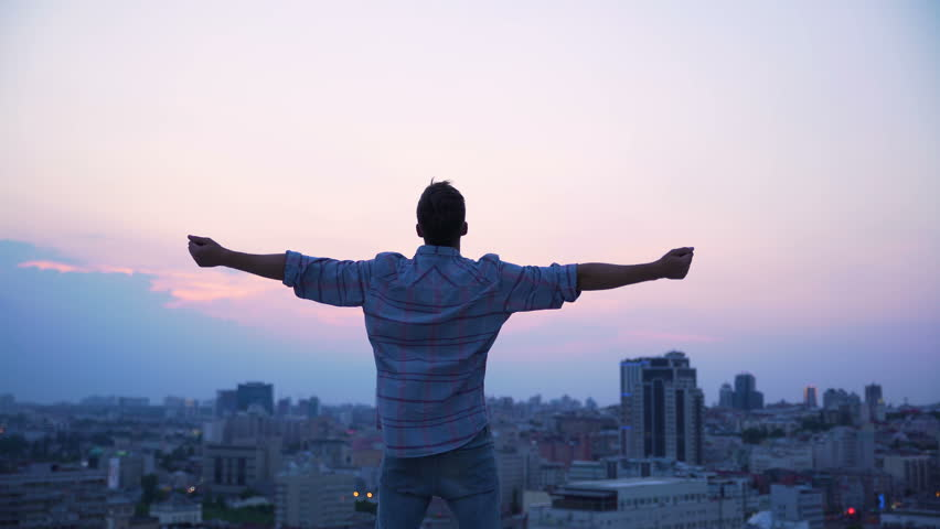 Man throwing his hands on roof edge, enjoying freedom, believe future success. Confident male enjoying city sunrise, achievement and inspiration. Happy tourist on skyscraper top, victory and purpose  | Shutterstock HD Video #1007372011