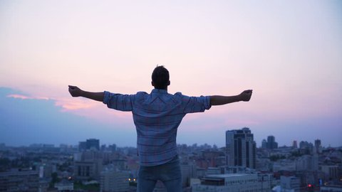 Man throwing his hands on roof edge, enjoying freedom, believe future success. Confident male enjoying city sunrise, achievement and inspiration. Happy tourist on skyscraper top, victory and purpose