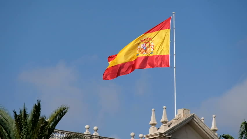 Flag of Spain. Red and yellow Spanish flag waving in the wind on a flagpole against the clear blue sky.