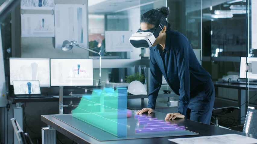 In the Office Professional Woman Wearing Augmented Reality Headset Interacts with Infographics Showing Statistics.  She Leans on the Table with Animated 3D Models Showing Company's Growth.