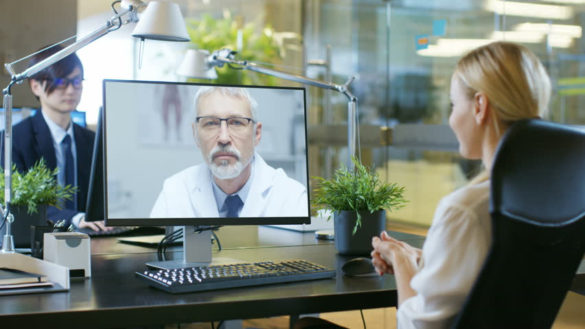 In the Office Businesswoman Talks with Her Doctor On the Video Call She Made with Personal Computer. Senior Physician Consults Attractive Blonde Woman.