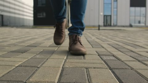 The one guy slowly confidence walks along the town footway in blue jeans and stylish brown leather shoe. Point of view from first person on legs close up. Autumn cold weather, pedestrian go up front