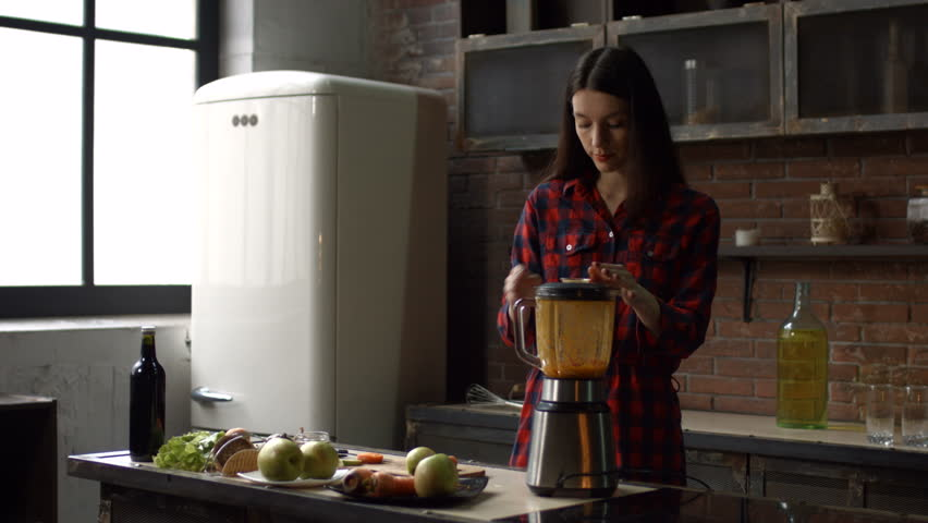 Stunning brunette woman blending food ingredinents with blender to make healthy detox smoothie in her kitchen. Attractive housewife preparing raw fresh juice using blender at home. Stabilized shot.