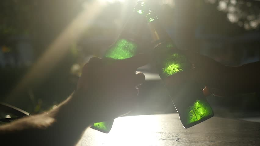 Close up of friends are clinking bottles through the sun with lens flare effects in cafe while sun is going down. 1920x1080