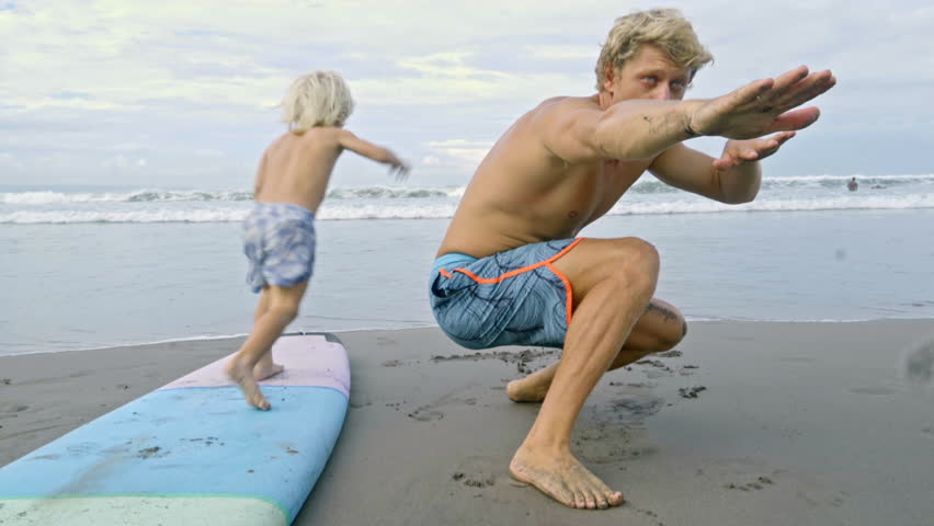 Father lying on stomach on beach teaching little son how to swim on surfboard and then kid running to ocean and playing with dog