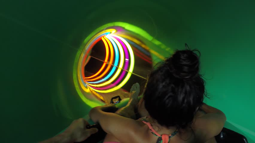 Young Mixed Race Couple Having Fun Riding Down in a Water Slide Tube. 4K Extreme Gopro Action Footage.
