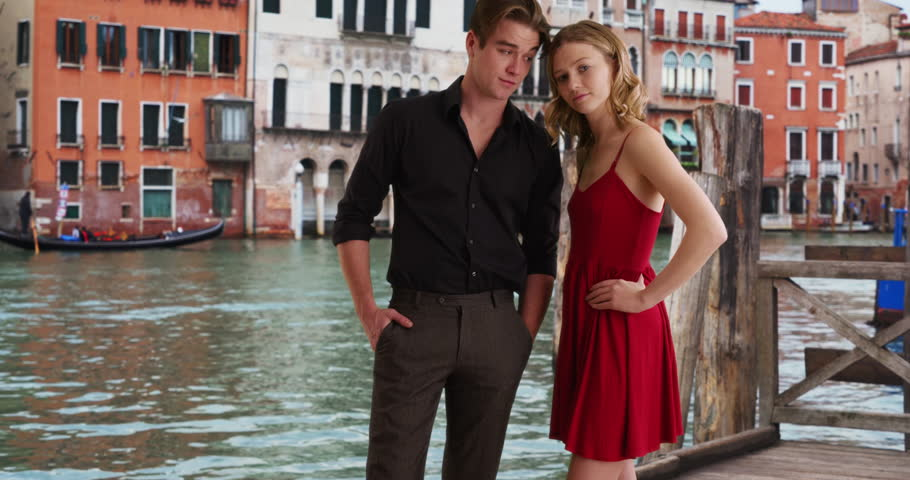 Sexy young Caucasian couple posing for a portrait in Venice. A man and woman standing by the Grand Canal looking at camera confidently. 4k | Shutterstock HD Video #1007466331