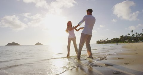 Romantic couple walking at beach at sunset dancing around holding hands. Young couple in love enjoying romance in casual elegant clothing on luxury beach vacation travel holidays, Lanikai, Oahu Hawaii
