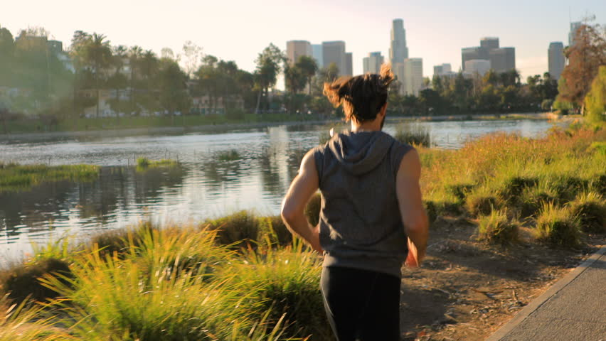 Athletic man jogs around a small lake in Los Angeles. Buildings of Los Angeles skyline can be seen in the distance. | Shutterstock HD Video #1007502289