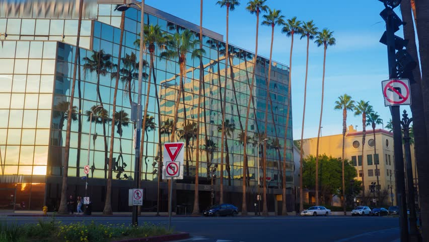 Hyperlapse view of city buildings and sky reflecting in office building glass wall background. Hollywood Blv, Los Angeles, California. 4K UHD. | Shutterstock HD Video #1007509384