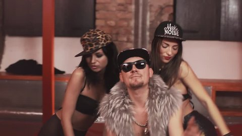Rich caucasian hip hop man in fur vest with glasses and snapback with sexy girls in underwear sitting on bed covered in money rapping