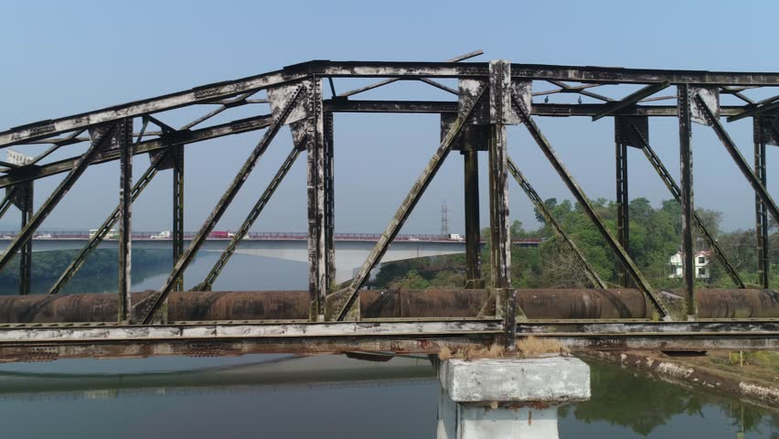 Drone flight along old, lengthy and rusty truss-type aqueduct over the river. Aerial view. | Shutterstock HD Video #1007525983