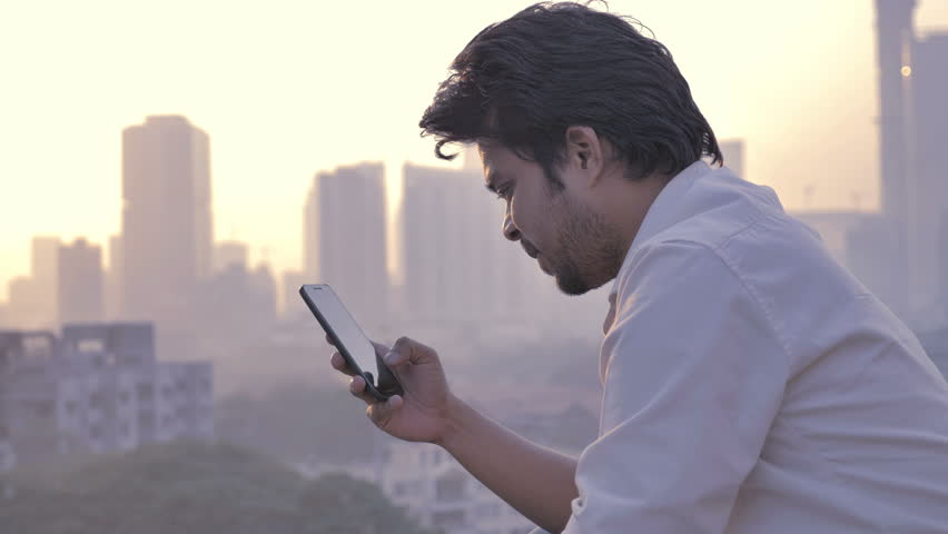 A young man typing a text message on a mobile phone against the vibrant and beautiful city skyline. A young attractive male using smartphone or cellphone to type a SMS or email against setting sun