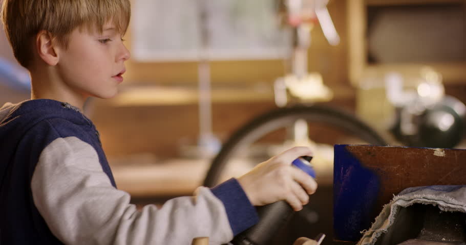 Cute young boy is painting a piece of wood | Shutterstock HD Video #1007537962