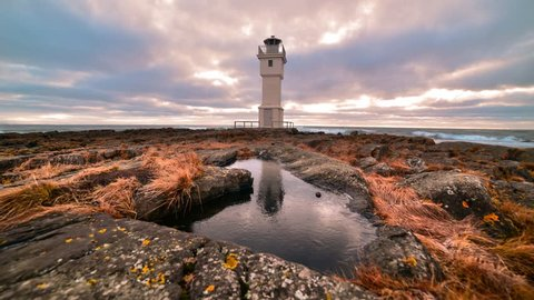 Old lighthouse with reflection and moving clouds timelapse video - Iceland, Akranes