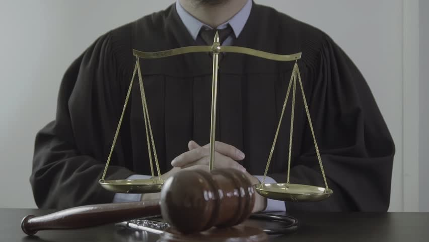 Front view of judge hand striking mallet with stethoscope at desk in courtroom in slow motion,Medical law and justice concept