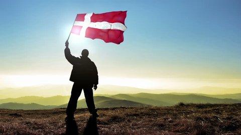 Successful silhouette man winner waving Danish flag on top of the mountain peak. Cinemagraph LOOP background