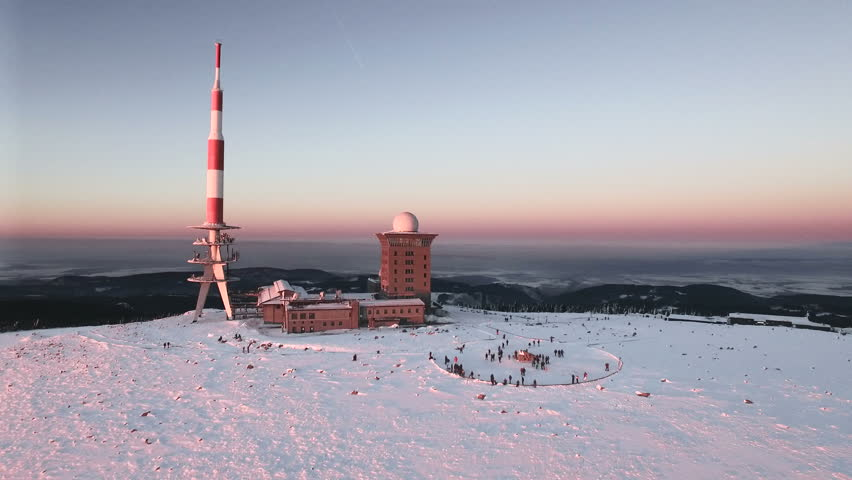 Aerial view of the Brocken peak in the Harz mountains in winter during sunset | Shutterstock HD Video #1007553061