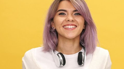 Close up view of happy woman in warm cardigan and headphones showing peace gesture at camera over yellow background