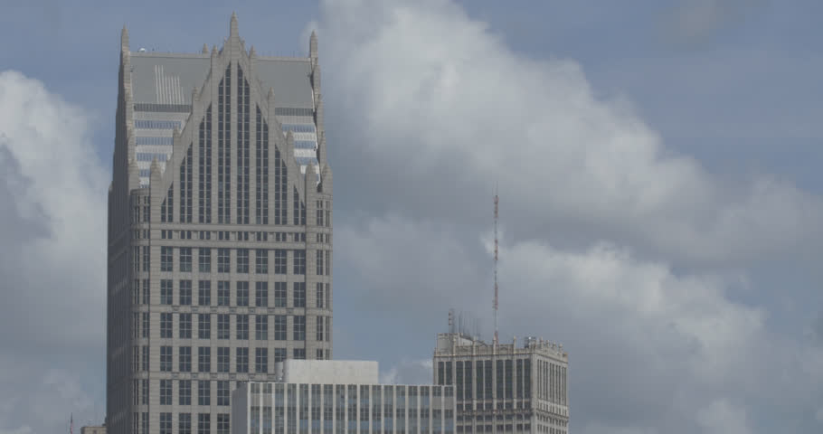Close up shot of clouds moving behind skyscrapers and the One Detroit Center building in Detroit.