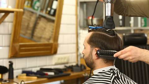 Barber blowdrying and combing hair of client using hairdrier and brush in Barbershop. Profile of young man having his hairstyle done at barber's, hd