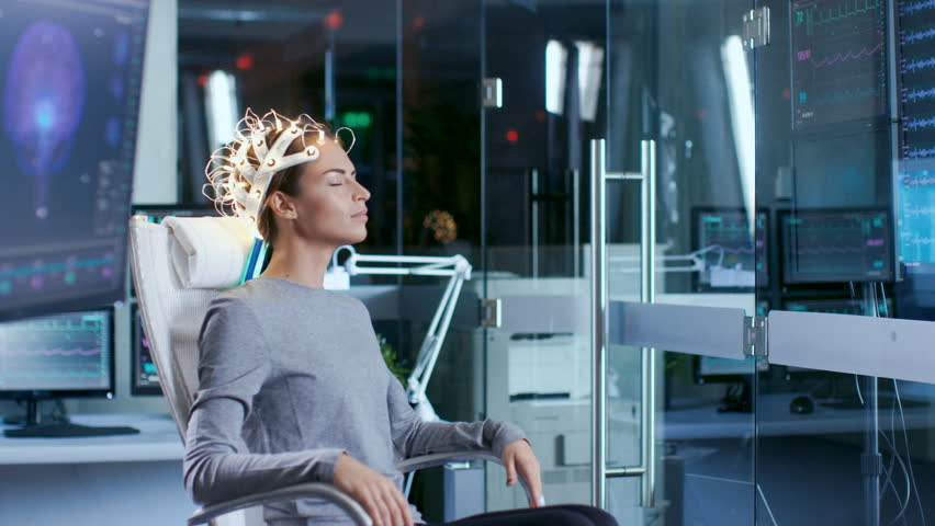 Woman Wearing Brainwave Scanning Headset Sits in a Chair while Scientist Adjusts the Device, Uses Tablet Computer. In the Modern Brain Study Laboratory Monitors Show EEG Reading.Shot on RED EPIC-W 8K