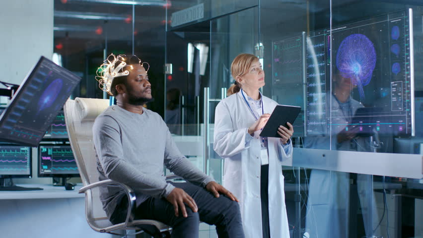 Man Wearing Brainwave Scanning Headset Sits in a Chair while Scientist with Tablet Computer Supervises Process. In the Modern Brain Study Laboratory Monitors Show EEG Reading and Brain Model.