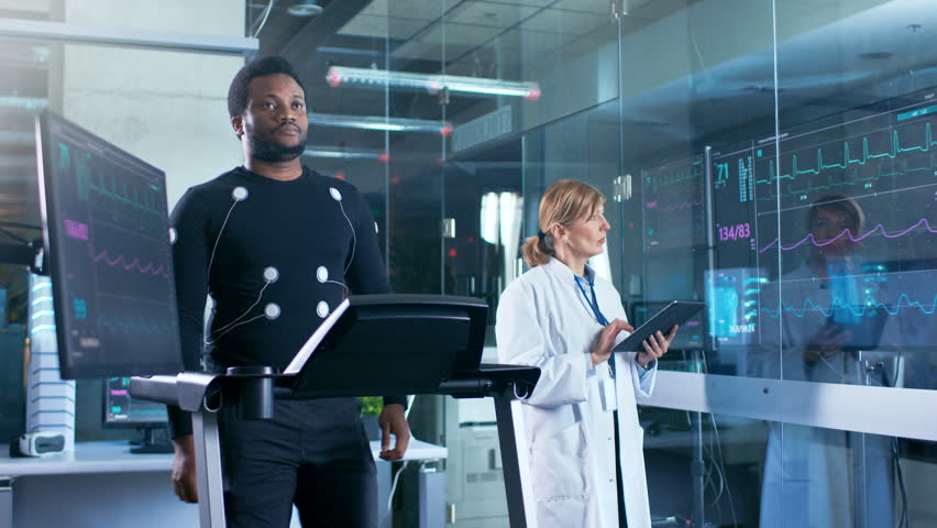 Male Athlete Walks on a Treadmill with Electrodes Attached to His Body while Sport Scientist Supervises Reads EKG Status. In the Background Laboratory with High-Tech Equipment. Shot on RED EPIC-W 8K