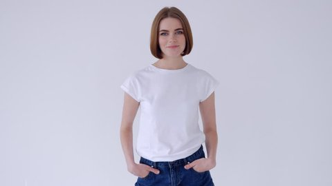 Beautiful woman folded arms while posing in jeans shorts and white T-shirt