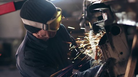 Workman with protective eyewear is grinding metal construction with circular saw.