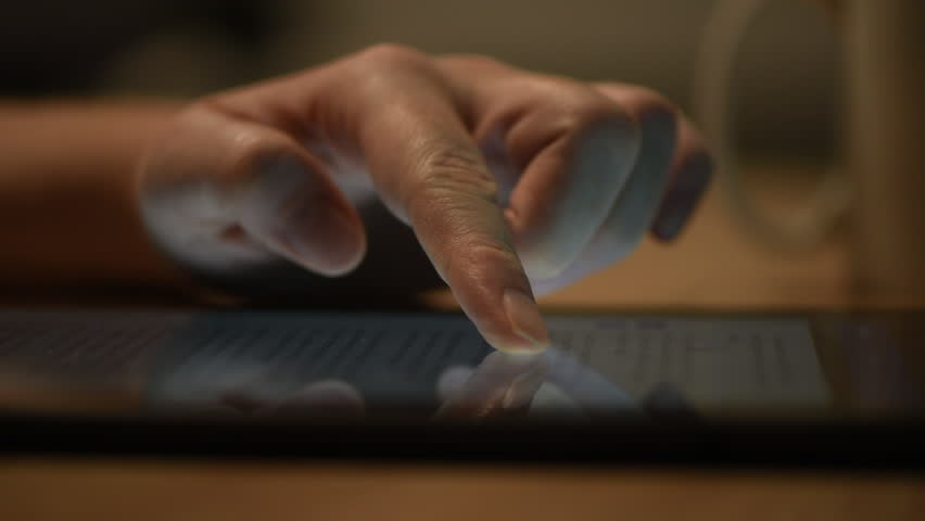 Woman reading online news on digital tablet, close up of hands using device | Shutterstock HD Video #1007635114