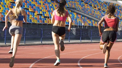 Multiethnic female athletes running on stadium on sunny day, workout and health