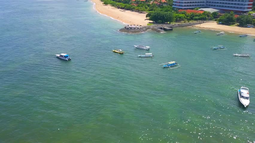 Aerial footage sanur beach bali. View from above with coastline and tree also wooden boats called jukung tied on shore. Flying over helipad