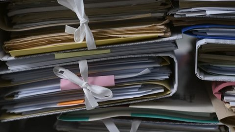 Office workers adding files on stacks of paperwork: work overload and management concept