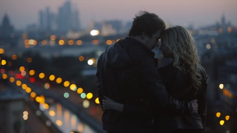 couple in rock-n-roll style standing on the roof in evening time at blured city lights background